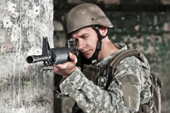 Young soldier behind obstacle. Young soldier in ruined building behind obstacle, aiming. air soft gun player Stock Images