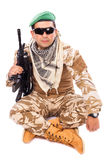 Young soldier with beret and glasses holding an automatic. Gun against white background Royalty Free Stock Photo