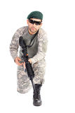 Young soldier with beret and glasses holding an automatic gun Stock Photos