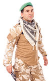Young soldier with green beret and arabian scarf looking at came Royalty Free Stock Photography