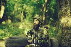 Young soldier on guard. Young soldier wirh bearded dusty tired face in military camouflage uniform with hanging camera and rifle in hand sitting on guard near stock image