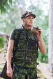 Young soldier with gun and flask in forest Stock Photography