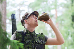 Young soldier with gun and flask in forest Royalty Free Stock Photos