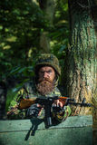 Young soldier with gun. Young soldier hipster with beard on dirty tired face in military ammunition and helmet standing on guard near tree and wooden board with Royalty Free Stock Photo