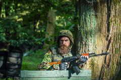Young soldier with gun. Young soldier hipster with beard on dirty tired face in military ammunition and helmet standing on guard near tree and wooden board with Stock Photography