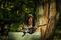 Young soldier with gun. Young soldier hipster with beard on dirty tired face in military ammunition and helmet standing on guard near tree and wooden board with Royalty Free Stock Images