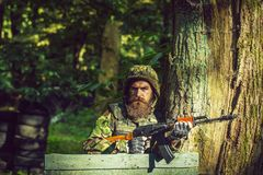 Young soldier with gun. Young soldier hipster with beard on dirty tired face in military ammunition and helmet standing on guard near tree and wooden board with royalty free stock image