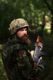 Young soldier with gun. Young soldier with sad bearded face in military helmet and camouflage with gun on forest background Stock Image