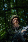 Young soldier with gun. Young soldier with sad bearded face in military helmet and camouflage with gun on forest background Stock Images