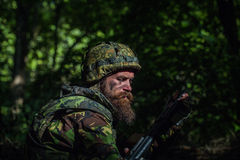Young soldier with gun. Young soldier with sad bearded face in military helmet and camouflage with gun on forest background Royalty Free Stock Images