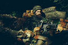 Young soldier with gun. Young soldier with sad bearded face in military helmet and camouflage with gun on ruined bricks background in forest Royalty Free Stock Photos