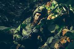 Young soldier with gun. Young soldier with sad bearded face in military helmet and camouflage with gun on ruined bricks background in forest Royalty Free Stock Images
