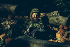 Young soldier with gun. Young soldier with sad bearded face in military helmet and camouflage with gun on ruined bricks background in forest Royalty Free Stock Photo