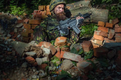 Young soldier with gun. Young soldier with sad bearded face in military helmet and camouflage with gun on ruined bricks background in forest Royalty Free Stock Image