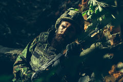 Young soldier with gun. Young soldier with sad bearded face in military helmet and camouflage with gun on ruined bricks background in forest Stock Photo