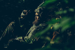 Young soldier with gun. Young soldier with sad bearded face in military helmet and camouflage with gun on ruined bricks background in forest Stock Photos