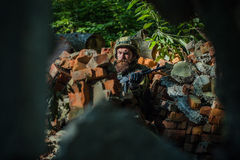 Young soldier with gun. Young soldier with sad bearded face in military helmet and camouflage with gun on ruined bricks background in forest Stock Images