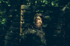 Young soldier with gun. Young soldier with sad bearded face in military helmet and camouflage with gun on wooden background Stock Images