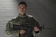 Young soldier holding assault rifle, horizontal. Military man holding assault rifle in dark room Royalty Free Stock Photo
