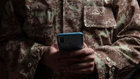 Young soldier holding a mobile phone standing on dark background stock photos