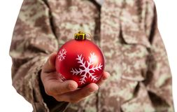 Young soldier holding a red christmas ball standing on white background royalty free stock photos