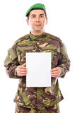 Young soldier holding white sheet of paper Royalty Free Stock Images