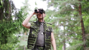 Young soldier or hunter with binocular in forest Stock Photos
