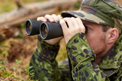 Young soldier or hunter with binocular in forest. Hunting, war, army and people concept - young soldier, ranger or hunter with binocular observing forest Stock Images