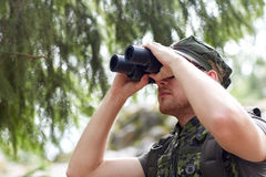 Young soldier or hunter with binocular in forest Stock Photo