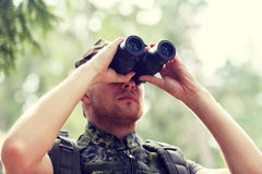 Young soldier or hunter with binocular in forest Royalty Free Stock Images