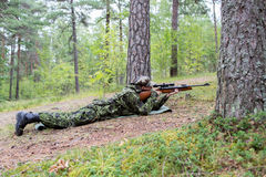 Young soldier or hunter with gun in forest Stock Image