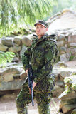 Young soldier or hunter with gun in forest Royalty Free Stock Photo