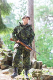 Young soldier or hunter with gun in forest. Hunting, war, army and people concept - young soldier, ranger or hunter with gun in forest Stock Image