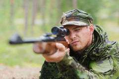 Young soldier or hunter with gun in forest. Hunting, war, army and people concept - young soldier, ranger or hunter with gun aiming and shooting in forest Stock Images