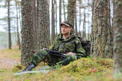 Young soldier or hunter with gun in forest Royalty Free Stock Image