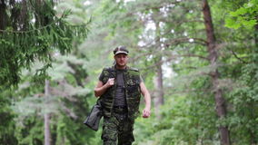 Young soldier or hunter with gun in forest stock footage