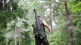 Young soldier or hunter with gun in forest stock video