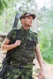 Young soldier or hunter with gun in forest Royalty Free Stock Photos