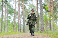 Young soldier or hunter with gun in forest. Hunting, war, army and people concept - young soldier, ranger or hunter with gun walking in forest stock photo