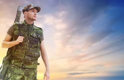 Young soldier or hunter with gun over sky. Hunting, army, military service and people concept - young soldier, ranger or hunter with gun over sky background Stock Image