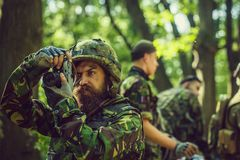 Soldier with camera in forest. Young soldier man with beard on grime serious face in ar y ammunition and helmet holding camera in his hands on background of royalty free stock images