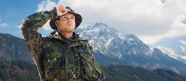 Young soldier in military uniform over mountains. Army, national service and people concept - young soldier or ranger wearing military uniform and jungle hat Stock Photo