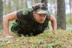 Young soldier or ranger doing push-ups in forest Stock Image