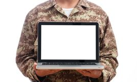 Young soldier showing a laptop with blank screen on white background. US Army. Young soldier showing a laptop computer with blank screen on white background royalty free stock photos