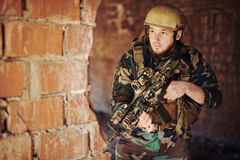 Young soldier. In uniform standing by brick wall with gun Stock Photo