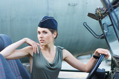 A young soldier woman posing in a military car. A young and attractive Caucasian soldier woman posing in a military car. The image is taken on an industrial Royalty Free Stock Photography
