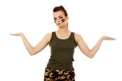 Young soldier woman presenting something on open palm.  royalty free stock photos