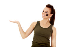 Young soldier woman presenting something on open palm.  royalty free stock photography