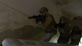 Young soldiers on a mission to kill terrorists ascending on stairs to first floor of a ruined building in search of the objective stock footage