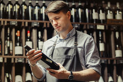 Young sommelier holding bottle of red wine in cellar Royalty Free Stock Images